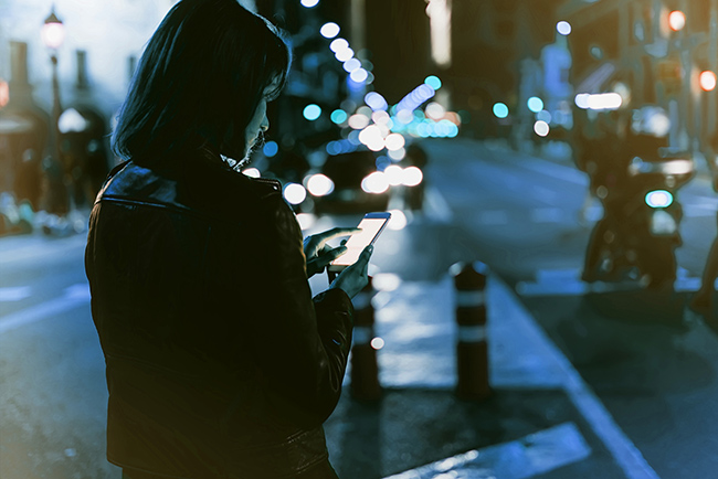 Woman using her phone at night.