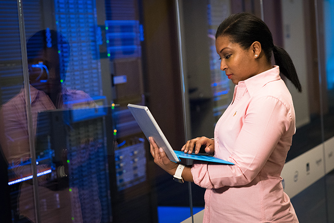 African American woman working in a server room.