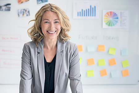 Woman wearing a suit, smiling in front of a wall with charts and sticky notes on it.